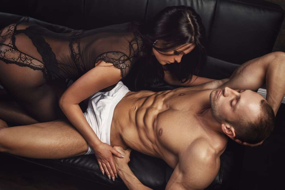 Sexy couple on leather sofa