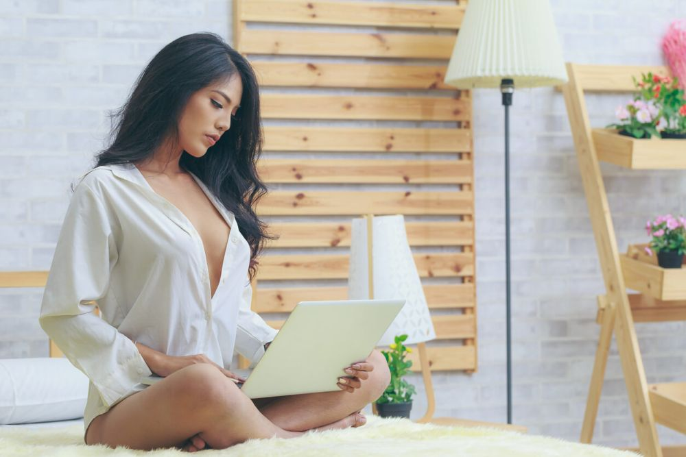 Asian woman in white shirt with laptop in the bedroom