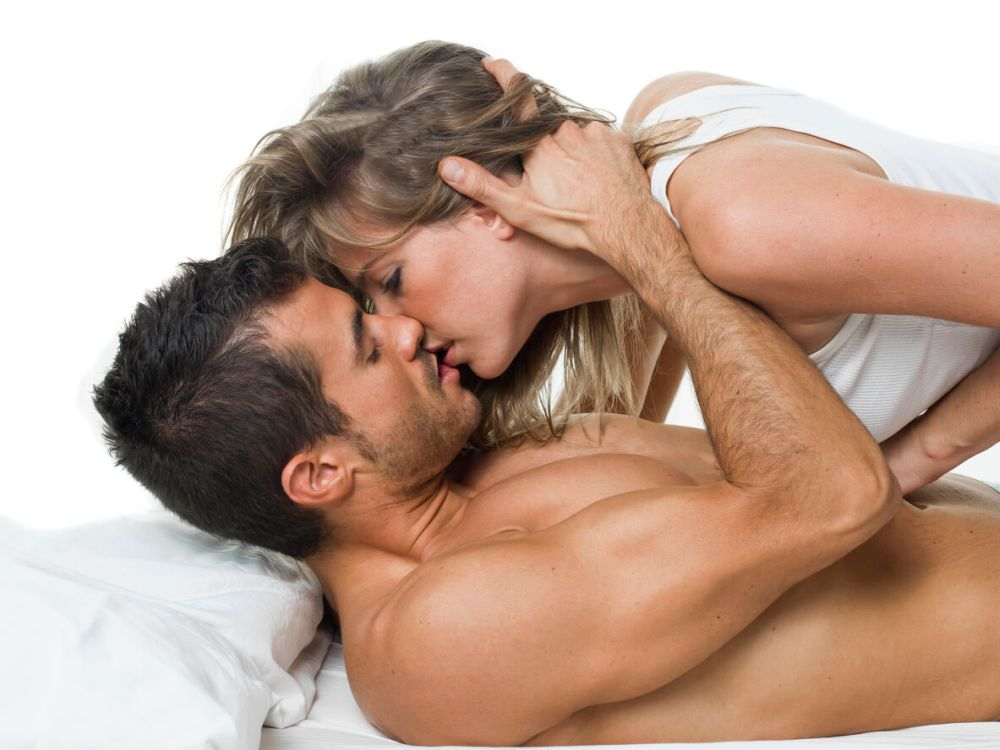 Attractive couple in love under white bed