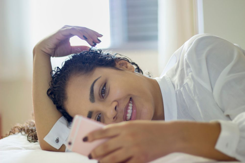 Happy young woman looking at mobile phone